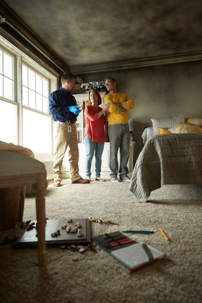 Technician Inspecting Fire Damaged Bedroom with Concerned Couple